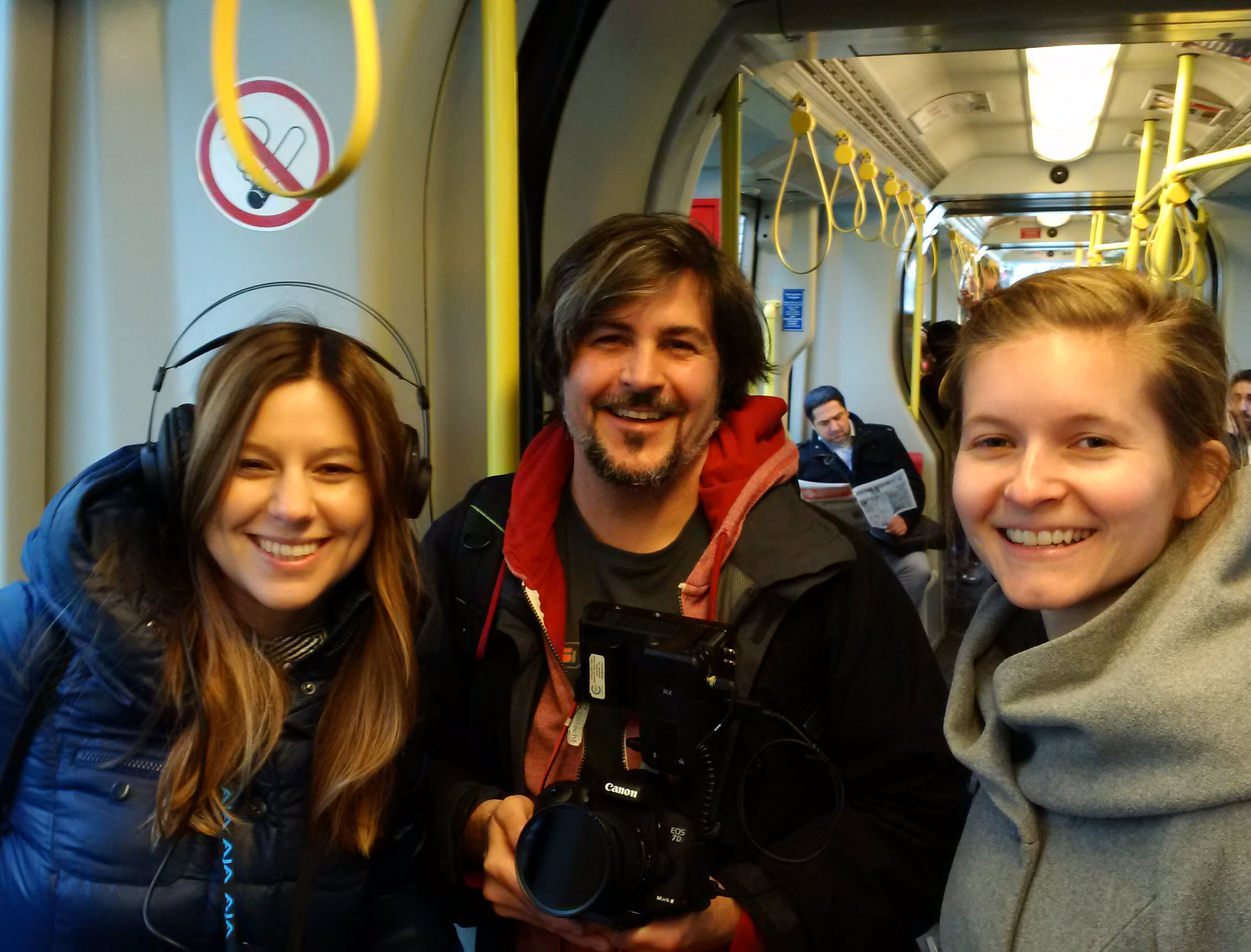 Three people smile at the camera in the tram.